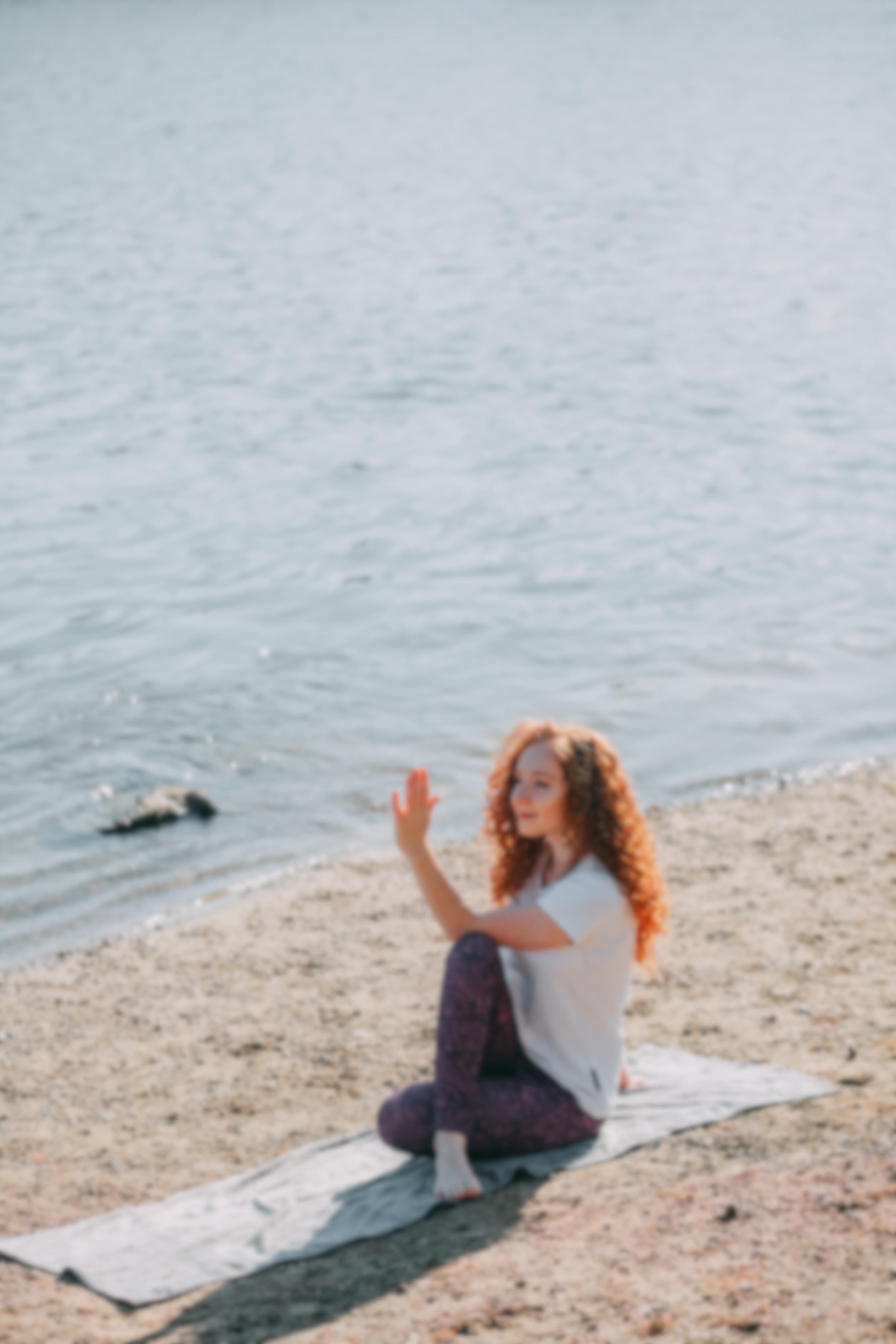 Woman Doing Yoga On Beach
